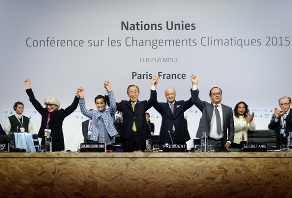 PARIS, FRANCE - DECEMBER 12: Executive Secretary of the United Nations Framework Convention on Climate Change (UNFCCC) Christiana Figueres (L 2), Secretary General of the United Nations Ban Ki Moon (C), Foreign Affairs Minister and President-designate of COP21 Laurent Fabius (R 2), and France's President Francois Hollande (R) raise hands together after adoption of a historic global warming pact at the COP21 Climate Conference in Le Bourget, north of Paris, on December 12, 2015. (Photo by Arnaud BOUISSOU/COP21/Anadolu Agency/Getty Images)